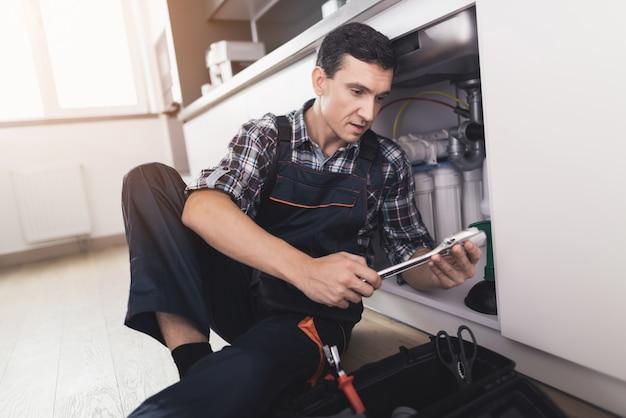 De jonge loodgieter zit dichtbij de gootsteen met tablet