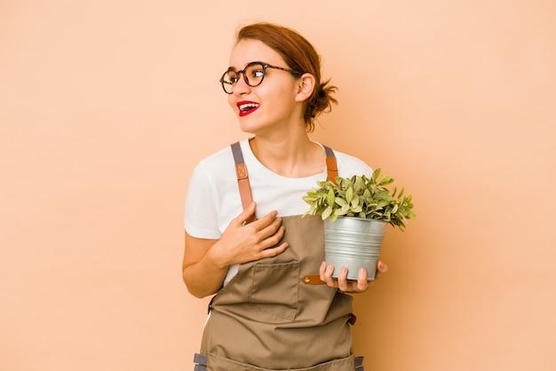De jonge magere arabische tuinmanvrouw kijkt opzij glimlachend, vrolijk en aangenaam.