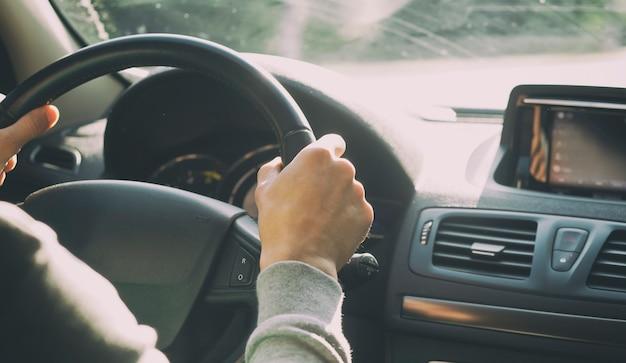 De jonge man besturen van de moderne auto op asfaltweg