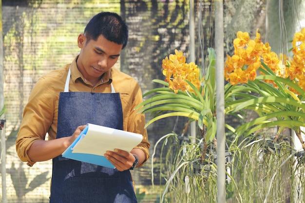 De jonge man die eigenaar is van de orchideetuin, controleert de orchidee voordat deze bij de klant wordt afgeleverd.