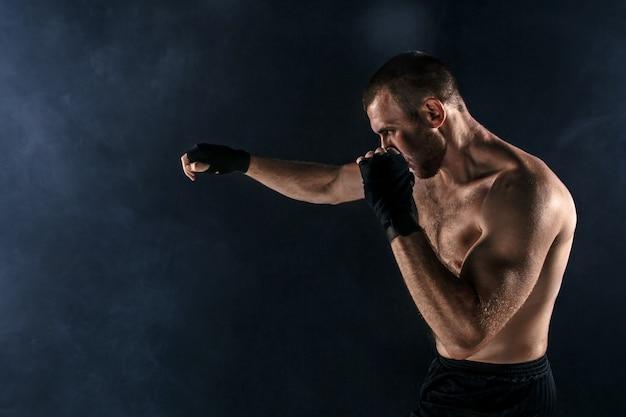 De jonge man die op zwarte copyspace kickboxing