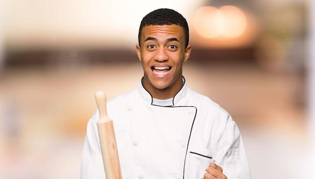 De jonge man die van de afro amerikaanse chef-kok een overwinning in winnaarpositie vieren op unfocused achtergrond
