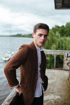 De jonge man die zich voordeed op een pier met uitzicht op zee