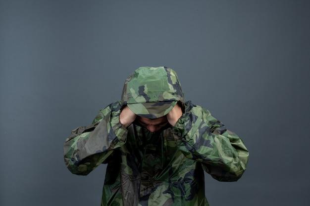 De jonge man draagt een camouflageregenjas en toont verschillende gebaren.