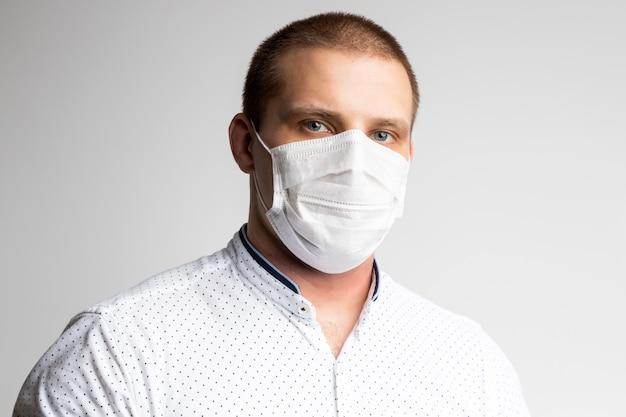 De jonge man draagt een masker om luchtvervuiling, nevel en pm 2.5 stof- en rookvervuiling op wit te voorkomen. medische bescherming tegen door de lucht verspreide ziekten, coronavirus. de mens is bang om griep te krijgen