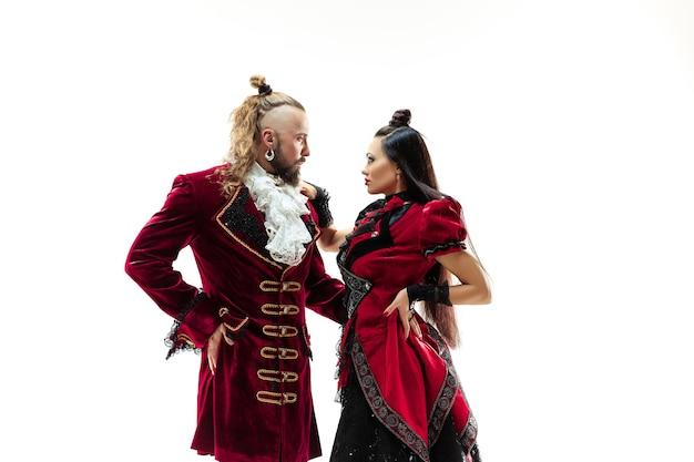 De jonge man draagt een traditioneel middeleeuws kostuum van markies die zich voordeed in de studio met vrouw als markiezin. fantasie, antiek, renaissance-concept