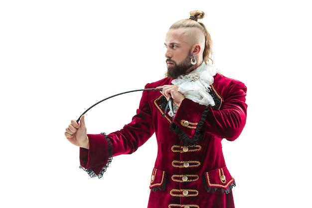 De jonge man draagt een traditioneel middeleeuws kostuum van markies poseren in de studio met zweep. fantasie, antiek, renaissance-concept