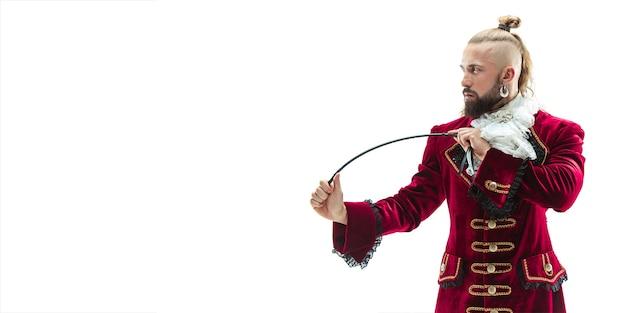 De jonge man draagt een traditioneel middeleeuws kostuum van markies poseren in de studio met zweep