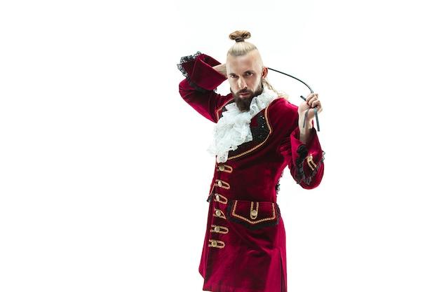 De jonge man draagt een traditioneel middeleeuws kostuum van markies poseren in studio met zweep.
