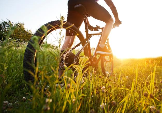 De jonge man fietst over het pad met veel gras en bloemen in het midden van het veld