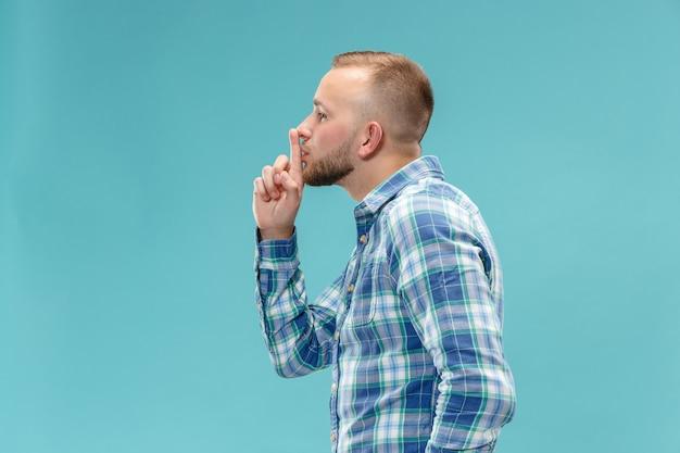 De jonge man fluistert een geheim achter haar hand over blauwe ruimte