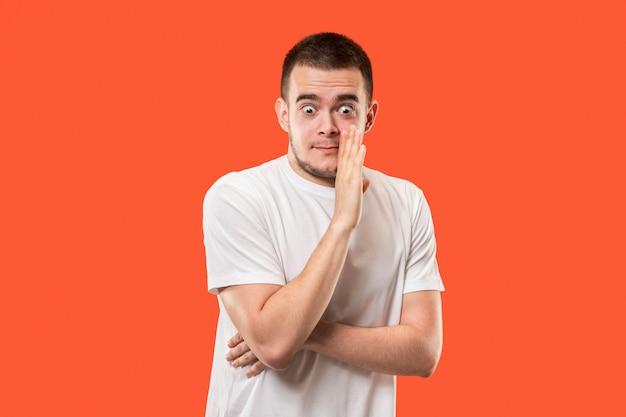 De jonge man fluistert een geheim achter haar hand over oranje ruimte