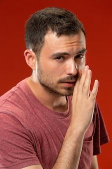 De jonge man fluistert een geheim achter haar hand over rode muur