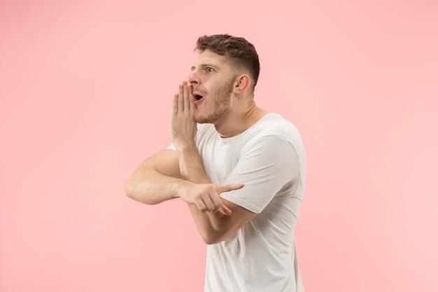 De jonge man fluistert een geheim achter haar hand over roze achtergrond