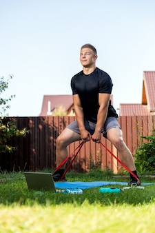 De jonge man gaat in de zomerdag thuis sporten in de achtertuin. jonge sportman met blond haar die hurkzit met sportrubber op mat, er is een laptop, een bal, dumbeels.
