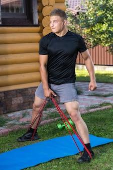 De jonge man gaat in de zomerdag thuis sporten in de achtertuin. jonge sportman met blond haar schudt handen met sportrubber op mat, er is een bal, dumbeels.
