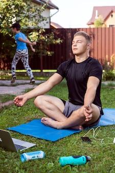 De jonge man gaat in de zomerdag thuis sporten in de achtertuin. vrolijke sportman met blond haar mediteert in lotushouding, rustend op de mat in de tuin