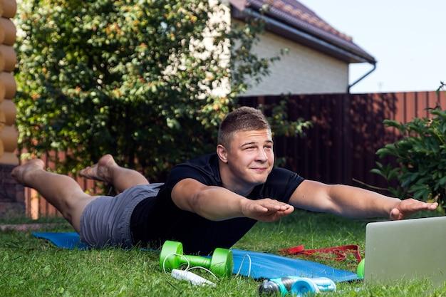 De jonge man gaat sporten thuis in de achtertuin in de zomerdag... vrolijke sportieve man die zich uitstrekt, plank doet, er zijn in laptop, halters
