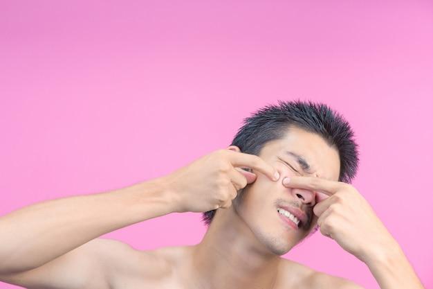 De jonge man gebruikt zijn handen om puistjes in zijn gezicht en het roze te persen.