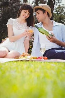 De jonge man giet aan vrouwenwijn in een glas tijdens een picknick