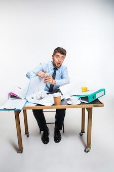 De jonge man heeft een complete puinhoop op de werkplek, hij kan zijn ruimte niet organiseren en belangrijke documenten vinden. concept van de problemen van de kantoormedewerker, zaken, reclame, dagelijkse problemen.