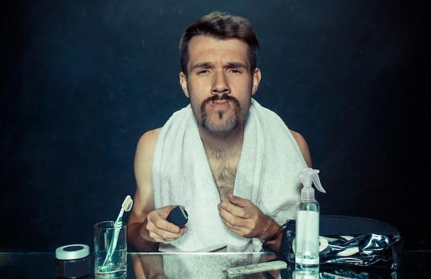 De jonge man in de slaapkamer die voor de spiegel zit die thuis zijn baard krabt. menselijke emoties concept en problemen met de huid