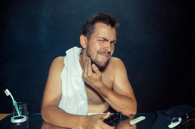 De jonge man in de slaapkamer die voor de spiegel zit die thuis zijn baard krabt. menselijke emoties concept