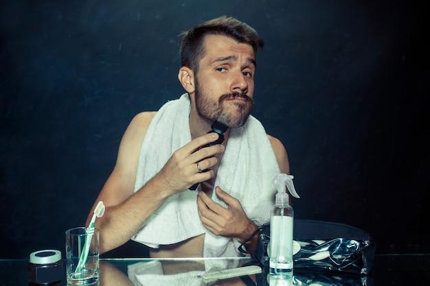 De jonge man in de slaapkamer die voor de spiegel zit die thuis zijn baard krabt. menselijke emoties en levensstijlconcept