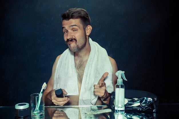 De jonge man in de slaapkamer die voor de spiegel zit die thuis zijn baard krabt