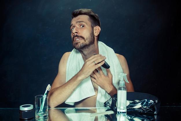 De jonge man in de slaapkamer zit voor de spiegel zijn baard thuis te krabben. menselijke emoties concept