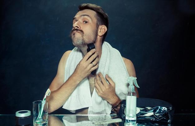 De jonge man in de slaapkamer zit voor de spiegel zijn baard thuis te krabben. menselijke emoties en levensstijlconcept