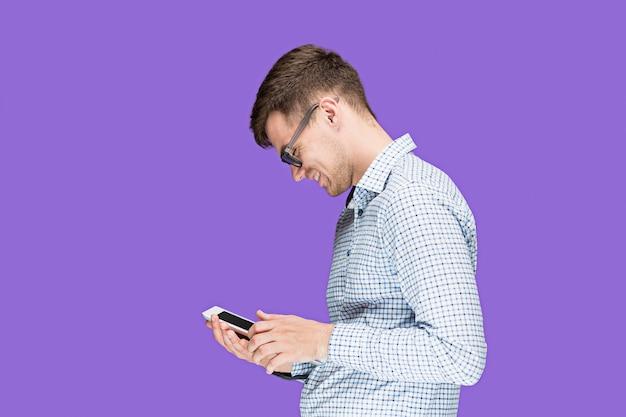 De jonge man in een overhemd die aan laptop op lila studioin werkt