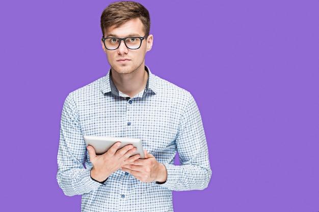 De jonge man in een shirt dat op laptop op lila wal werkt