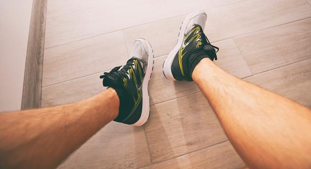 De jonge man is klaar voor de ochtendrennen en zit op trappen in nieuwe sneakers