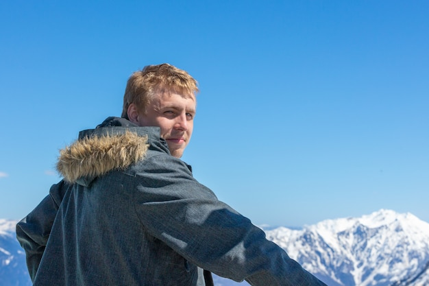 De jonge man keerde zijn rug toe en keek naar het berglandschap.