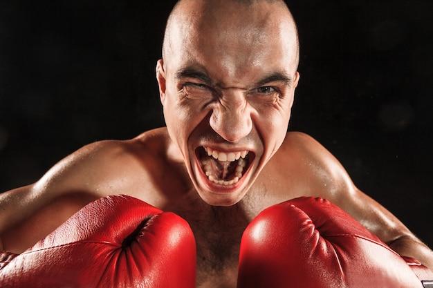 De jonge man kickboksen op zwart met schreeuwend gezicht