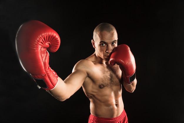 De jonge man kickboksen op zwart