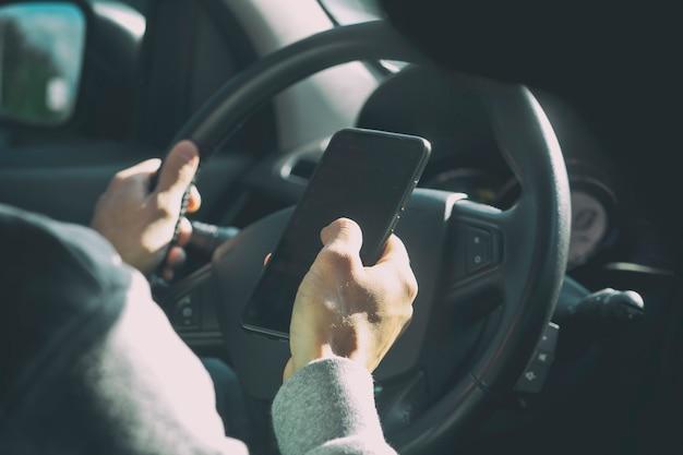 De jonge man kijkt op zijn telefoon terwijl hij de auto bestuurt