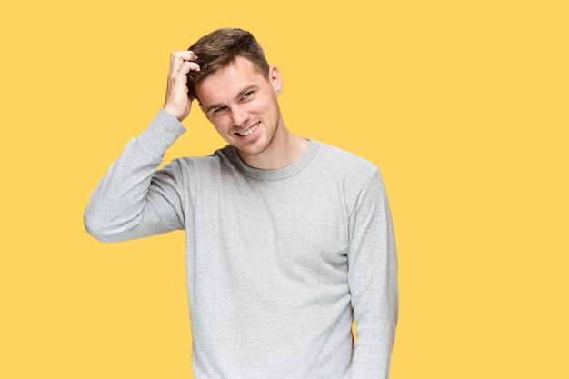 De jonge man lacht en kijkt naar de camera op gele studio achtergrond