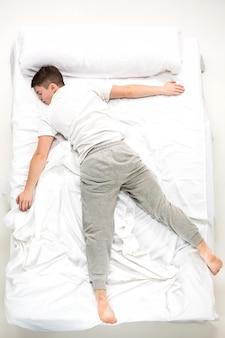 De jonge man liggend in een bed