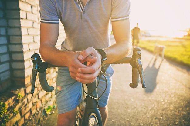 De jonge man met fiets loopt door de weg