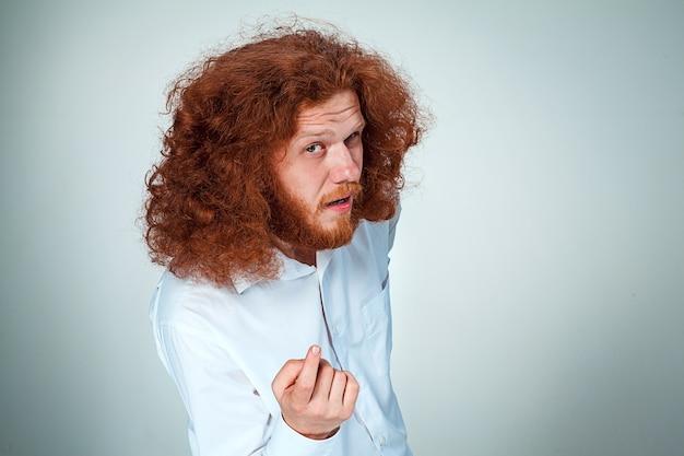 De jonge man met lang rood haar die camera bekijkt die iemand lokt