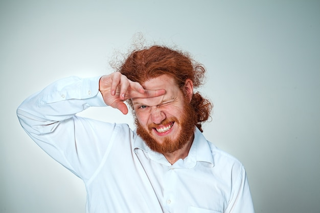 De jonge man met lang rood haar die naar de camera kijkt en zijn ogen verknalt