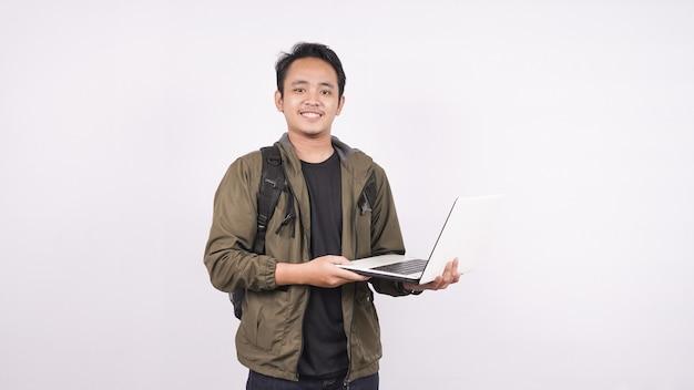 De jonge man met tas op een witte ruimte met laptop