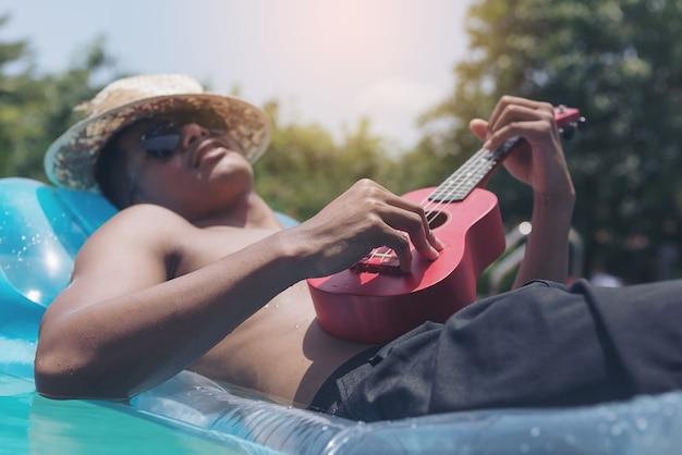 De jonge man ontspant en speelt ukulele op een rubberen dobber in een buitenbad in de zon