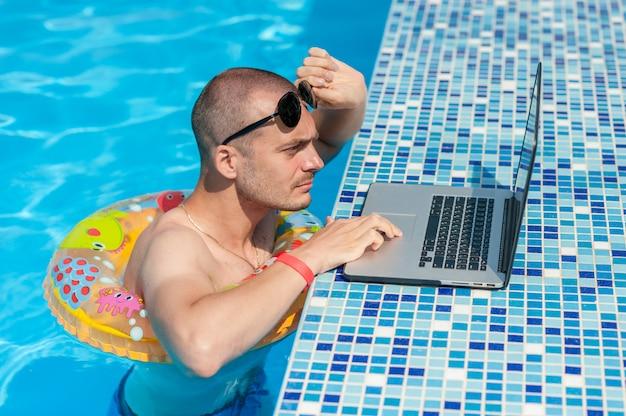 De jonge man op zomervakantie met de laptop, zaken online. afstand thuiskantoor in zwembad in rubberen ring op quarantaine
