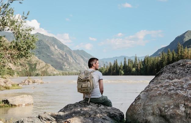 De jonge man reist door bergen