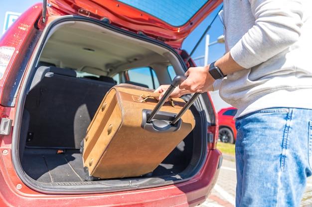 De jonge man schat bagage in auto kofferbak