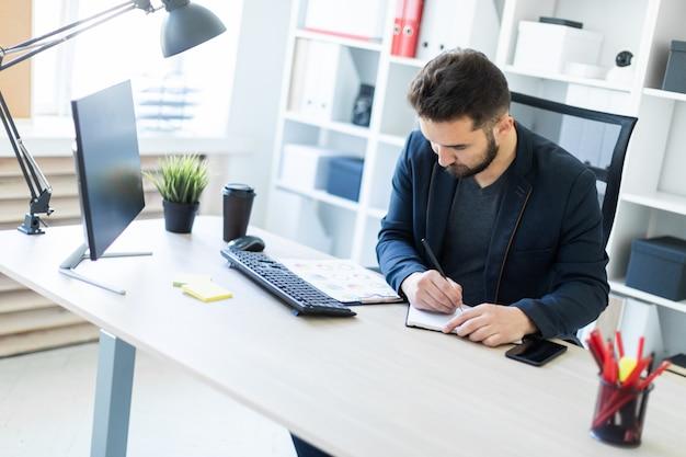 De jonge man werkt op kantoor op een computer bureau met documenten, diagrammen en telefoon.