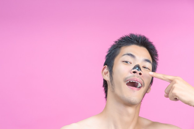 De jonge man wijst met zijn vinger naar de zwarte cosmetica, het slijm en het roze.